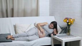 Szczęśliwa ciężarna kobieta leżąca na kanapie w domu nakłada krem na żołądku w postaci uśmiechu zdjęcie wideo