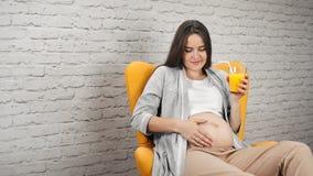 Szczęśliwa ciężarna młoda kobieta muska nagiego dużego brzucha trzyma świeżego soku pomarańczowego środka strzał zbiory