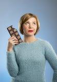 Szczęśliwa czekoladowa nałogowiec kobieta trzyma dużego prętowego usta plamiący i szalony z podnieceniem twarzy wyrażenie Zdjęcie Stock