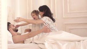 Szczęśliwa czuła rodzina trzy: matka, ojciec i córka ma zabawę w łóżku, zbiory