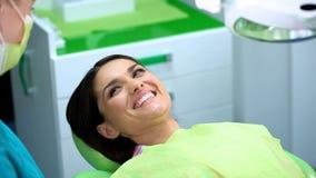 Szczęśliwa dama śmia się przy dentystyka gabinetem po procedury, checkup w klinice zdjęcia stock