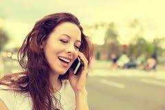 Szczęśliwa dama opowiada na telefonu komórkowego odprowadzeniu na ulicie Zdjęcia Royalty Free