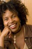 Szczęśliwa dojrzała amerykanin afrykańskiego pochodzenia kobieta ono uśmiecha się w domu fotografia stock