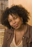 Szczęśliwa dojrzała amerykanin afrykańskiego pochodzenia kobieta ono uśmiecha się w domu zdjęcia stock