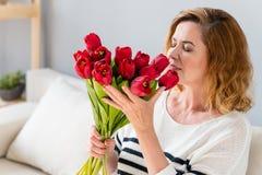 Szczęśliwa dojrzała dama z bukietem tulipany zdjęcia stock