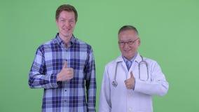 Szczęśliwa dojrzała Japońska mężczyzna lekarka z młodym człowiekiem daje aprobatom wpólnie zbiory