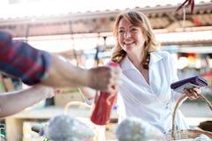 Szczęśliwa dojrzała kobieta płaci dla świeżych organicznie warzyw w lokalnym rynku zdjęcia royalty free