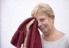 Szczęśliwa dojrzała kobieta wyciera jej twarz z czerwonym ręcznikiem w gym odzieży zdjęcia stock