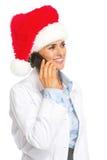 Szczęśliwa doktorska kobieta w Santa kapeluszowym opowiada telefonie komórkowym Obrazy Stock