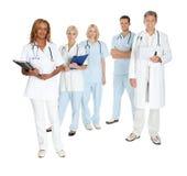 Szczęśliwa drużyna lekarki i chirurdzy na bielu Zdjęcia Royalty Free
