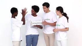 Szczęśliwa drużyna wolontariuszi trzyma darowizny pudełko zbiory wideo
