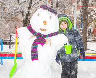 Szczęśliwa dzieciak chłopiec bawić się z bałwanem na zima spacerze w naturze Dziecko ma zabawę przy Bożenarodzeniowym czasem plen Zdjęcia Royalty Free