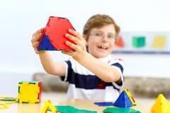 Szczęśliwa dzieciak chłopiec z szkłami ma zabawę z budynkiem i tworzy geometryczne postacie, uczący się mathematics i geometrię zdjęcia royalty free