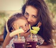 Szczęśliwa dzieciak dziewczyna i śmieszna emocjonalna matka pije jagody smoothie sok wpólnie w ulicznego lata plenerowej kawiarni zdjęcie royalty free