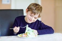 Szczęśliwa dzieciaka chłopiec je świeżej sałatki z pomidoru, ogórkowych i różnych warzywami, jako posiłek lub przekąska Zdrowy dz zdjęcia stock