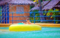 Szczęśliwa dzieciaka jeżdżenia zabawki wody łódź w aqua parku Zdjęcie Royalty Free