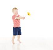 Szczęśliwa dziecko chłopiec daje teraźniejszego kwiatu uśmiecha się dziecko Obrazy Stock