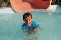 Szczęśliwa dziecko chłopiec ma zabawę w woda parku Zdjęcia Royalty Free