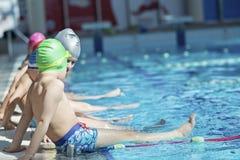 Szczęśliwa dziecko dzieciaków grupa przy pływackiego basenu klasy uczenie pływać obraz royalty free