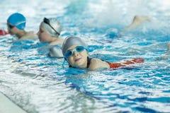 Szczęśliwa dziecko dzieciaków grupa przy pływackiego basenu klasy uczenie pływać zdjęcia stock