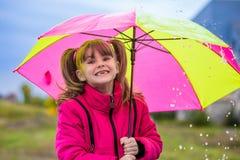 Szczęśliwa dziecko dziewczyna śmia się z parasolem w deszczu zdjęcie royalty free