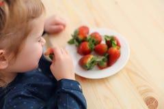 Szczęśliwa dziecko dziewczyna je truskawki w lato domu kuchni Zdjęcia Royalty Free
