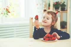 Szczęśliwa dziecko dziewczyna je truskawki w lato domu kuchni Fotografia Stock