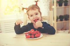 Szczęśliwa dziecko dziewczyna je truskawki w lato domu kuchni Obraz Royalty Free