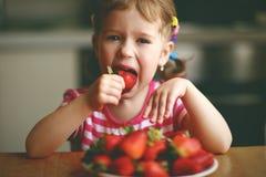 Szczęśliwa dziecko dziewczyna je truskawki w lato domu kuchni Zdjęcia Stock