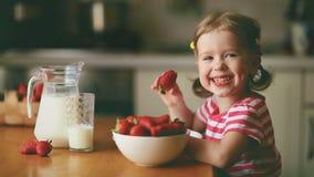 Szczęśliwa dziecko dziewczyna je truskawki w lato domu kuchni Obraz Stock