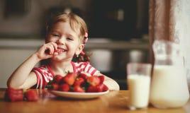 Szczęśliwa dziecko dziewczyna je truskawki w lato domu kuchni Fotografia Royalty Free