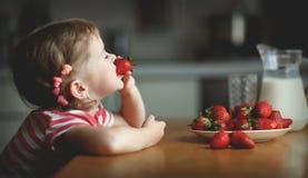 Szczęśliwa dziecko dziewczyna je truskawki w lato domu kuchni Obrazy Stock