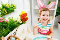 Szczęśliwa dziecko dziewczyna maluje jajka dla wielkanocy Obrazy Royalty Free