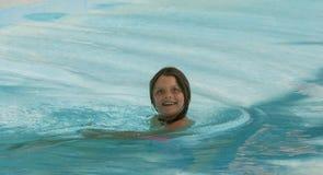 Szczęśliwa dziecko dziewczyna robi śmiesznemu szalonemu twarzy wyrażeniu i pływa w oceanie, Obrazy Stock