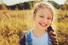 Szczęśliwa dziecko dziewczyna w cajgu kombinezonie bawić się na pogodnym polu Zdjęcie Stock