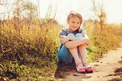 Szczęśliwa dziecko dziewczyna w cajgu kombinezonie bawić się na pogodnym polu, lato plenerowy styl życia zdjęcia stock
