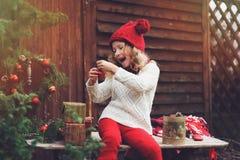 Szczęśliwa dziecko dziewczyna w czerwonych kapeluszu i szalika opakunkowych Bożenarodzeniowych prezentach przy wygodnym dom na ws Zdjęcia Royalty Free