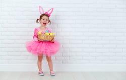 Szczęśliwa dziecko dziewczyna w kostiumowym Wielkanocnego królika króliku z koszem Zdjęcia Stock
