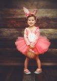 Szczęśliwa dziecko dziewczyna w kostiumowym Wielkanocnego królika króliku z koszykowymi jajkami Fotografia Stock