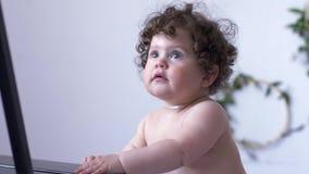 Szczęśliwa dziecko dziewczyna z kędzierzawym włosy na fotografii sesi w studiu na tle biel ściana zbiory