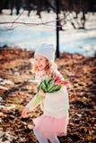 Szczęśliwa dziecko dziewczyna z tulipanu bukietem ma zabawę na spacerze w wczesnej wiośnie Zdjęcie Royalty Free
