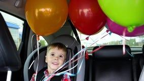 Szczęśliwa dziecko jazda w samochodzie Świąteczny nastrój, uśmiech, śmiech Balony w samochodzie Dziecka ` s urodziny zbiory wideo
