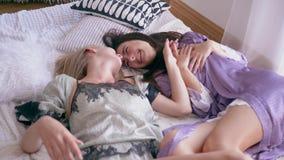 Szczęśliwa dziewczyna łaskocze siostry rozochocony weekend która kłama na leżance przy piżamy przyjęciem, zbiory wideo