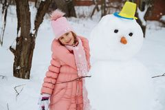 Szczęśliwa dziewczyna ślepiąca bałwanem od śniegu w zimie Obrazy Royalty Free