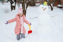 Szczęśliwa dziewczyna ślepiąca bałwanem od śniegu w zimie Fotografia Royalty Free