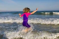 Szczęśliwa dziewczyna bawić się w fala obrazy stock