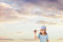 Szczęśliwa dziewczyna bawić się z trykotowym zabawkarskim samolotem zdjęcia stock