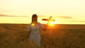 Szczęśliwa dziewczyna biega z zabawkarskim samolotem na kwiatu polu dziecko sztuki zabawki samolot nastolatków sen latanie i zdjęcie wideo