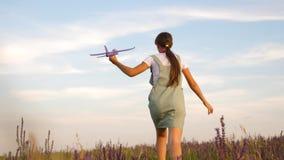 Szczęśliwa dziewczyna biega z zabawkarskim samolotem na kwiatu polu dziecko sztuki zabawki samolot nastolatków sen latanie i zbiory