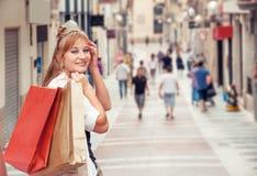 Szczęśliwa dziewczyna chodzi przez ulicy po robić zakupy Ona mienie zdjęcia royalty free